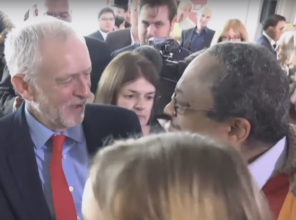 Jeremy Corbyn shakes the hand of Labour Party activist Marc Wadsworth, shortly after Wadsworth accused a Jewish member of parliament of being part of a media conspiracy at the unveiling of Labour's report on anti-Semitism in the party. Photo: Ruptly TV / YouTube