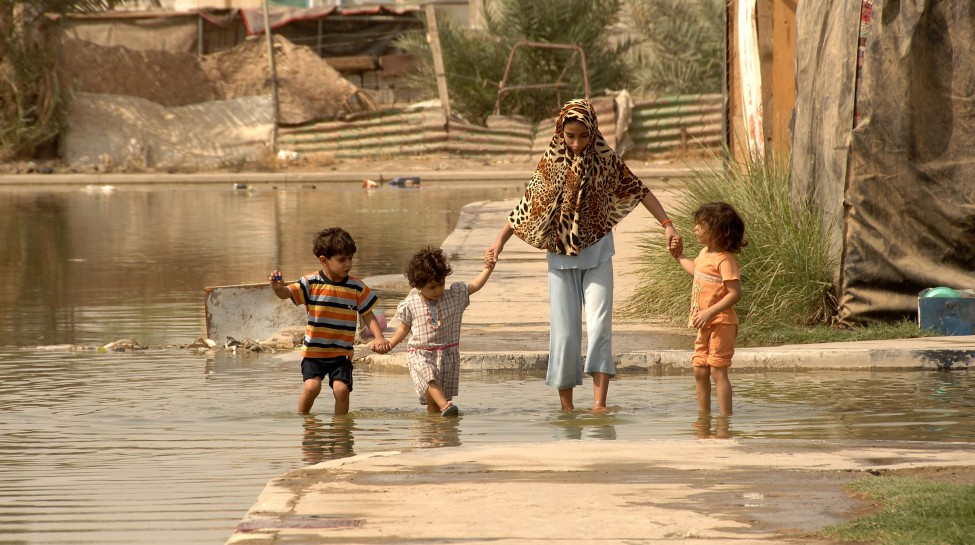 A family in Baghdad makes its way through streets flooded by a water main break. Photo: Spc. Charles Gill / flickr