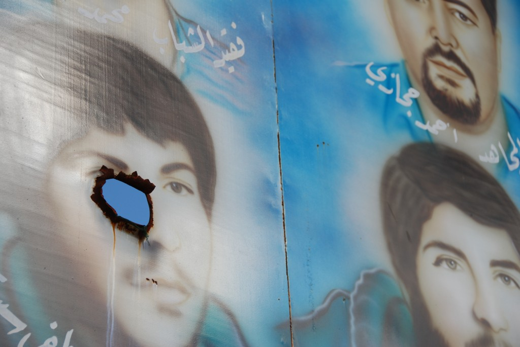 Shell hole in the portrait of a dead Hezbollah fighter painted on a signboard along the road from Tyre to Bint Jbeil in southern Lebanon. Photo: Paul Keller / flickr