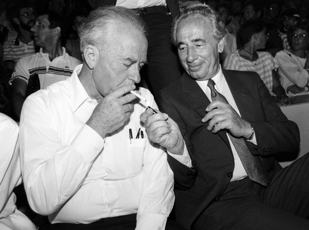 Prime Minister Shimon Peres lights the cigarette of Defense Minister Yitzhak Rabin, September 16, 1986. Photo: Moshe Shai / Flash90
