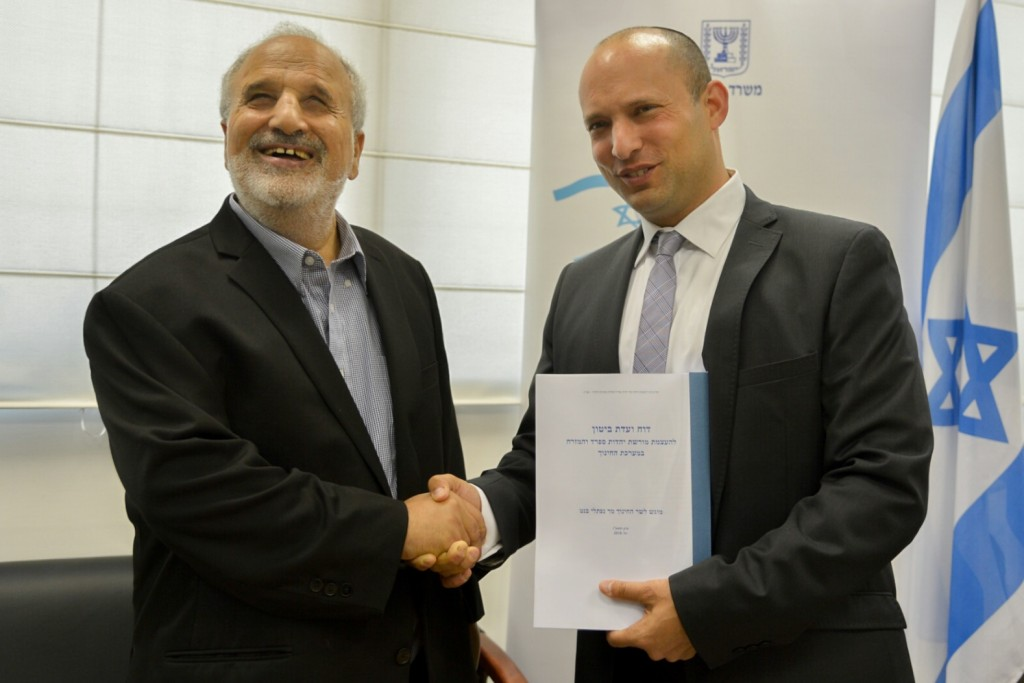 Mizrahi Israeli poet Erez Biton (L) hands the Biton Committee Report to Israeli Minister of Education Naftali Bennett. Photo: Flash90