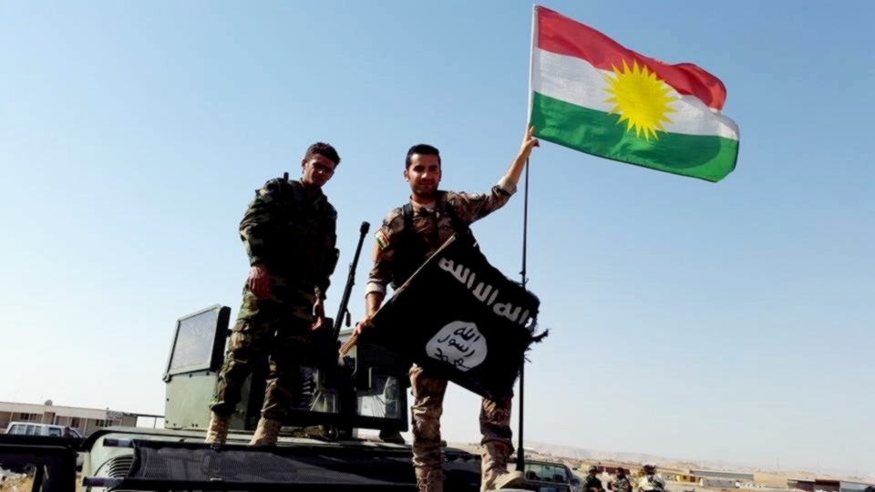 Peshmerga near Mosul remove the Islamic State flag and replace it with the Kurdish flag. Photo: Kurdish Struggle / flickr