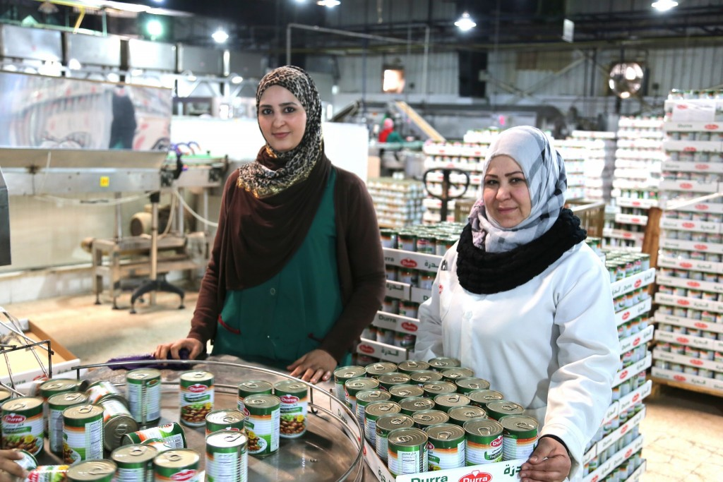 Anood from Jordan and Salma from Syria, working together in a Syrian-owned food processing factory in Jordan. Photo: Bea Arscott / UK Department for International Development