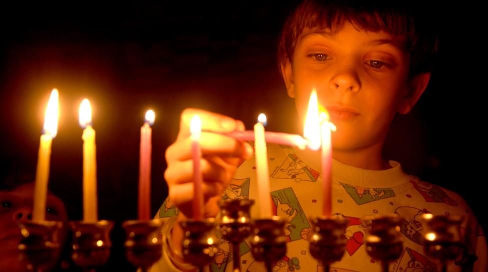 HANNUKA HOLIDAY. IN THE PHOTO, ISHAY OHAYON LIGHTSTHE 5TH HANNUKA CANDLE IN JERUSALEM.  çâ äçðåëä. áöéìåí, éùé àåçéåï îãìé÷ ðø çîéùé ùì çðåëä, áéøåùìéí.