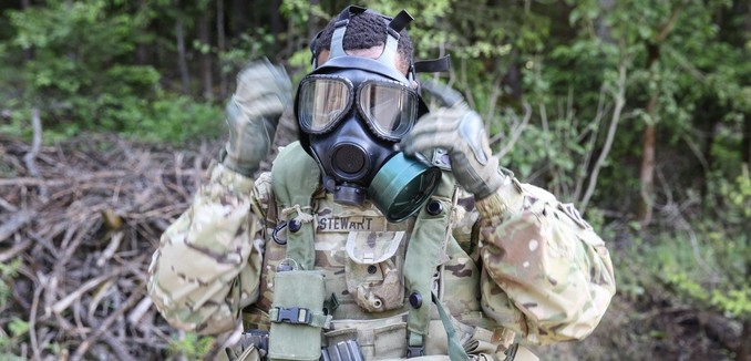 U.S. Army Sgt. Jimmy Lee Stewart of Alpha Company, 3rd Brigade Support Battalion, 1st Armored Brigade Combat Team, 3rd Infantry Division puts on his gas mask while conducting a complex attack during exercise Combined Resolve IV at the U.S. Army's Joint Multinational Readiness Center in Hohenfels, Germany, May 22, 2015.  Combined Resolve IV is an Army Europe directed exercise training a multinational brigade and enhancing interoperability with allies and partner nations. Combined Resolve trains on unified land operations against a complex threat while improving the combat readiness of all participants. The Combined Resolve series of exercises incorporates the U.S. Army's Regionally Aligned Force with the European Activity Set to train with European Allies and partners. The 7th Army JMTC is the only training command outside the continental United States, providing realistic and relevant training to U.S. Army, Joint Service, NATO, allied and multinational units, and is a regular venue for some of the largest training exercises for U.S. and European Forces. (U.S. Army photo by Spc. Shardesia Washington/Released)