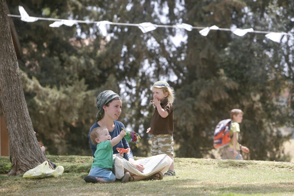 A family sits on the grass in the Jewish settlement of Susya, May 2009. Photo: Miriam Alster / Flash90