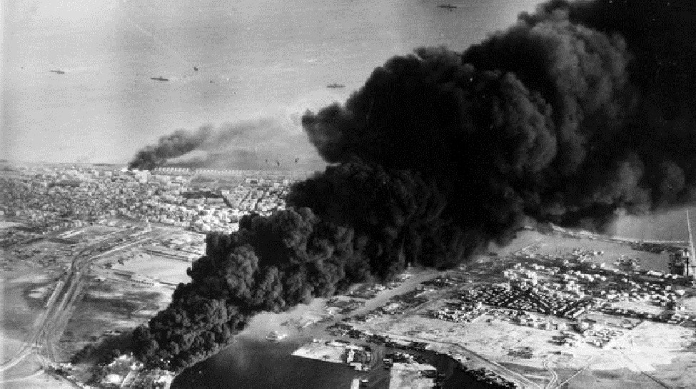 Smoke rises from oil tanks beside the Suez Canal hit during the initial Anglo-French assault on Port Said, November 5, 1956. Photo: Imperial War Museum