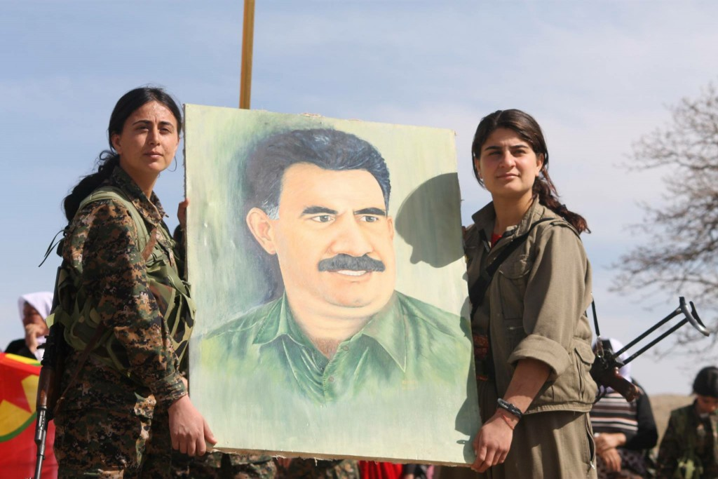 Soldiers from the YBŞ and PKK hold up a painting of their political leader, Abdullah Öcalan. Photo: Kurdish Struggle / flickr