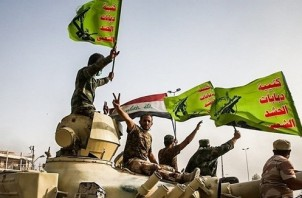 FeaturedImage_2017-10-18_WikiCommons_Raising_flag_of_Iraq_and_Popular_Mobilization_Forces_after_defeating_DAESH