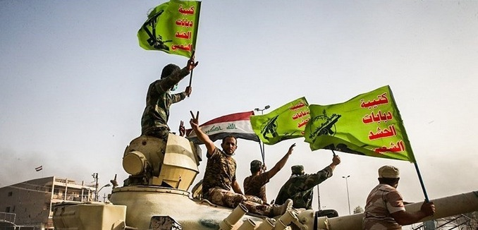 FeaturedImage_2017-11-21_WikiCommons_Raising_flag_of_Iraq_and_Popular_Mobilization_Forces_after_defeating_DAESH