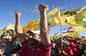 "Hezbollah supporters shout slogans and wave Hezbollah flags, during a rally commemorating ""Liberation Day"" which marks the withdrawal of the Israeli army from southern Lebanon in 2000, in the southern border town of Bint Jbeil, Lebanon, Sunday May 25, 2014. Hezbollah's leader Sheik Hassan Nasrallah is warning that hard-line foreign fighters in Syria pose a global threat as they return home. Nasrallah accused European countries of easing the flight of extremist fighters into Syria, where they are fighting against the rule of President Bashar Assad. (AP Photo/Hussein Malla)"